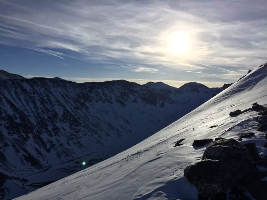 The sun peeking out from behind the clouds as we ascend to the top of Quandary Peak in February.