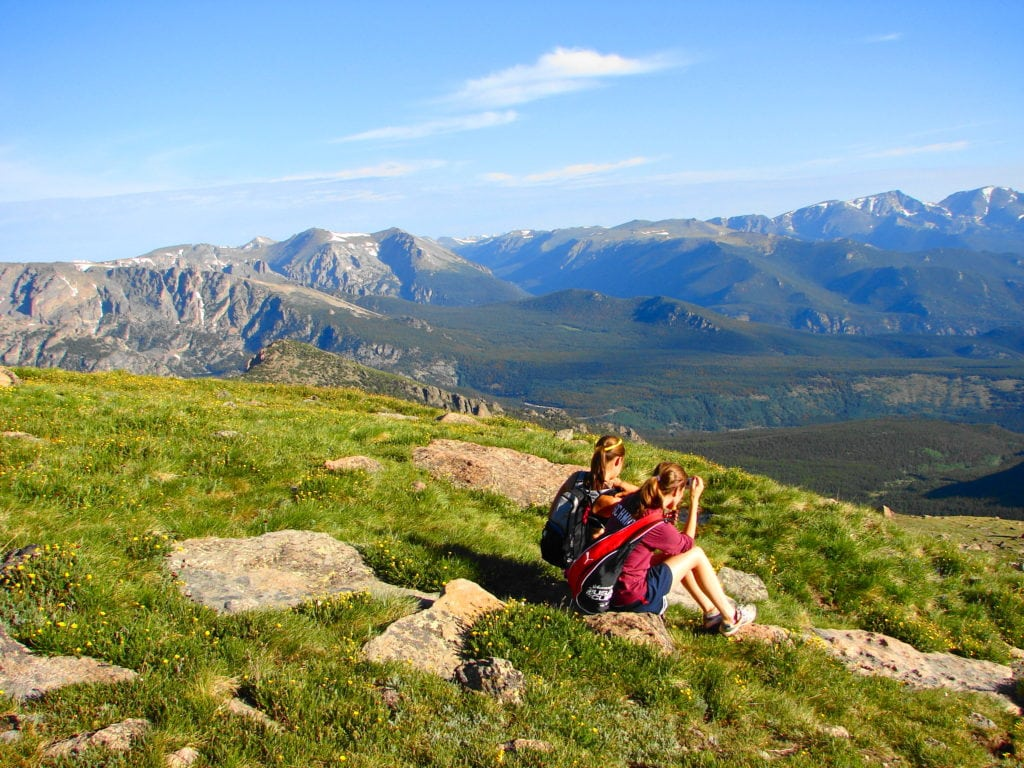 Two hikers sitting in the grass gazing out into Rocky Mountain National Park from the side of Long's Peak.