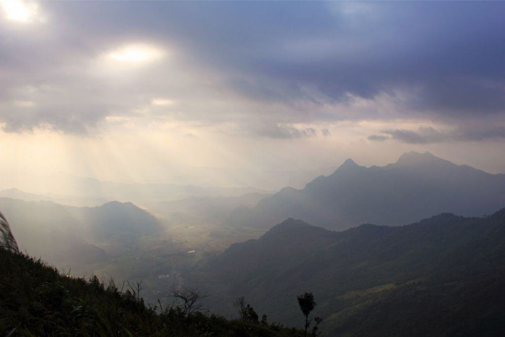 The sun rays peek out from behind the clouds at Phu Chi Fa in Northern Thailand.