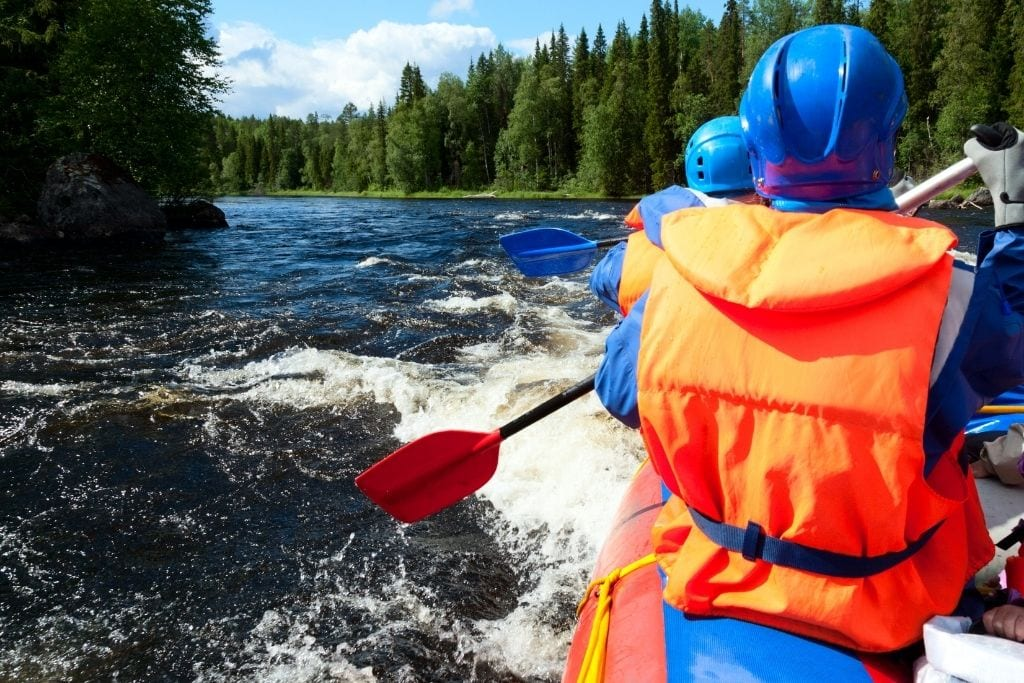 Two White Water Rafters Paddling Down The Deschutes River In Bend, Oregon On A Summer Day.