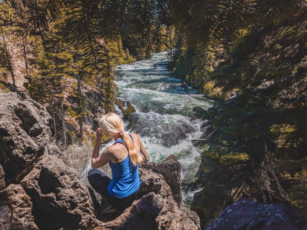 Laura Sitting In Front of Benham Falls, A Hiking Trail Near Bend, Oregon