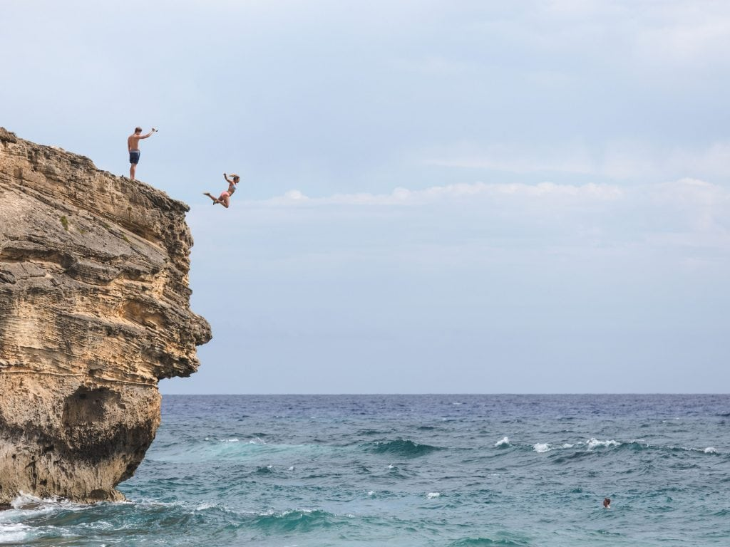 Two People Cliff Jumping On The Island of Kauai, One of the Best Things To Do.