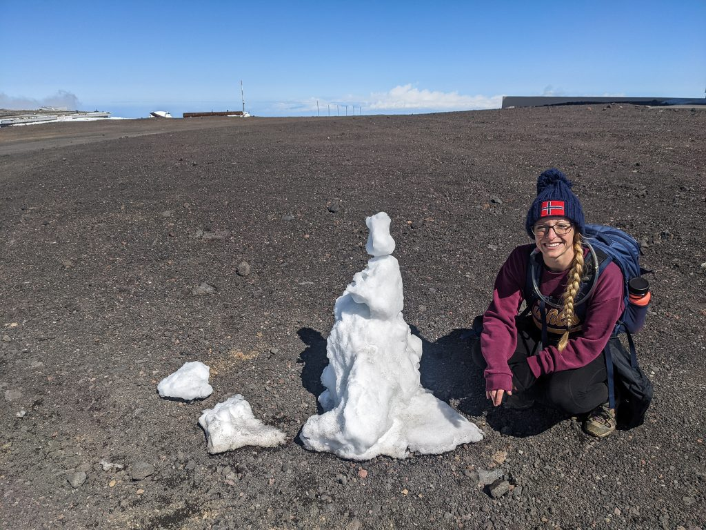 Laura Sitting Next To A Snowman At The Top of Mauna Kea.