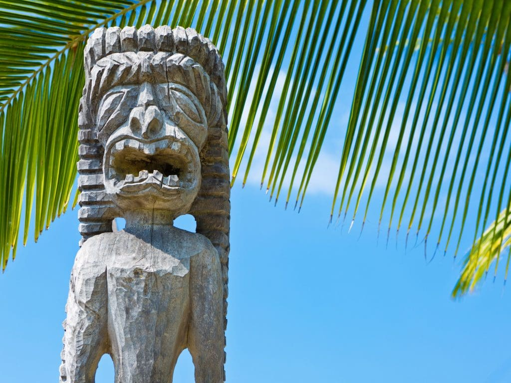An Ancient Wooden Hawaiian Carving In Front of A Palm Tree.