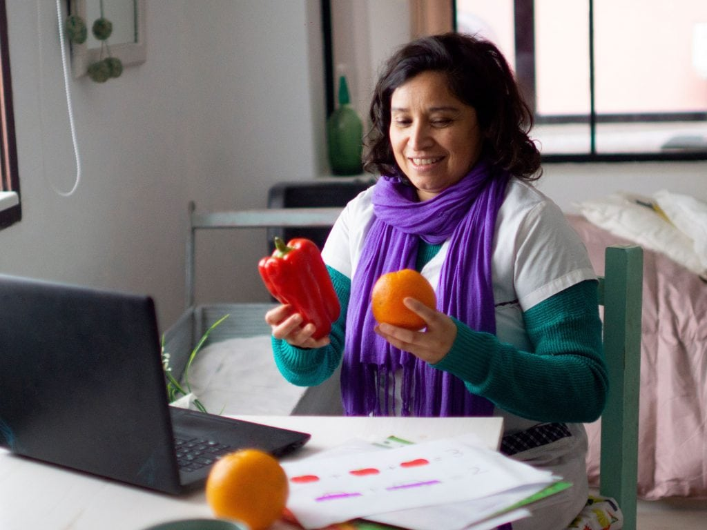 Online English Teacher Teaching To Her Student Using Fruit For Props.