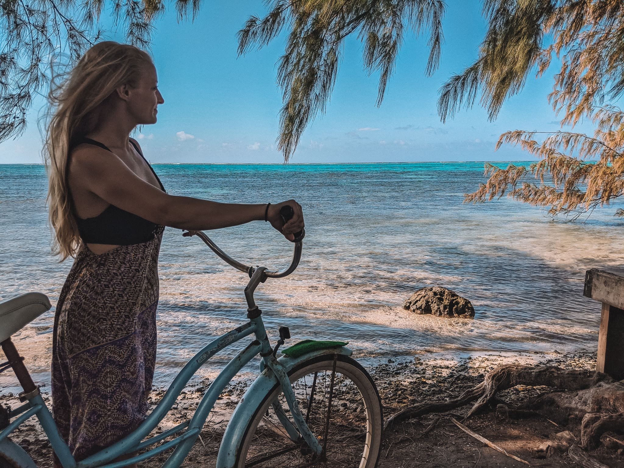 Standing With A Bike Gazing Out At The Ocean In French Polynesia.