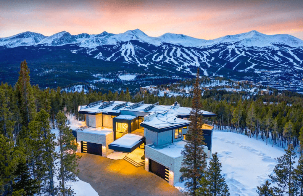 An Upscale Home With The Rocky Mountains In The Background.