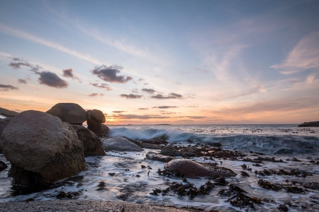 Oudekraal At Sunset With The Waves Crashing Into The Rocks.