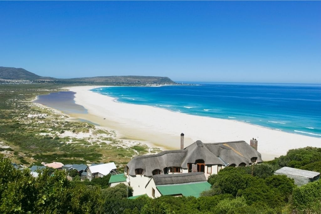 A Long Stretch of Long Beach With a House in the Foreground. One of the Best Beaches in Cape Town.