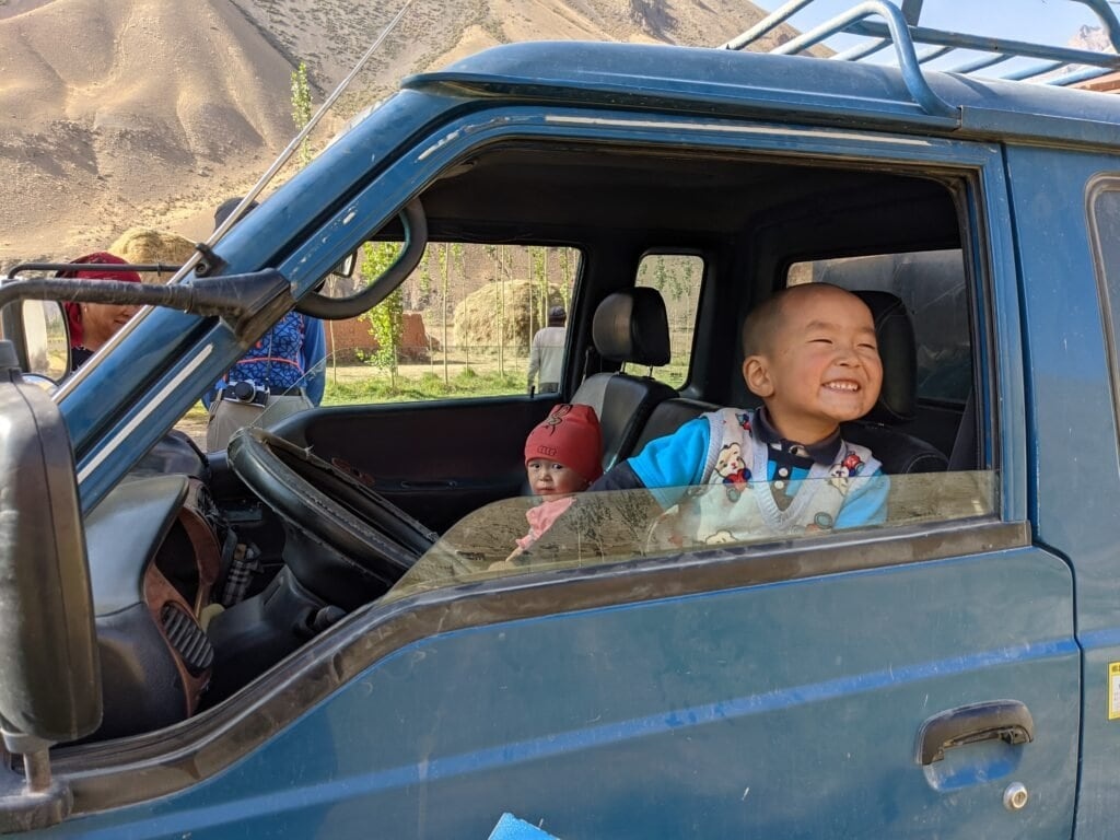 A Young Local Boy and Toddler Playing In A Truck In Kyrgyzstan.
